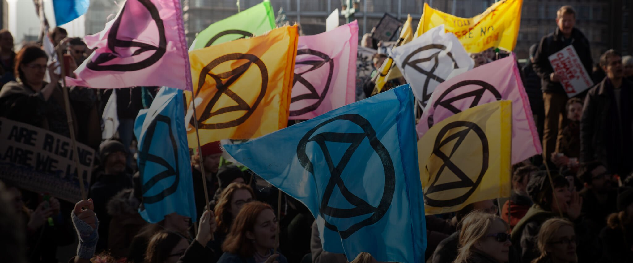 people protesting with colorful extinction rebellion flags