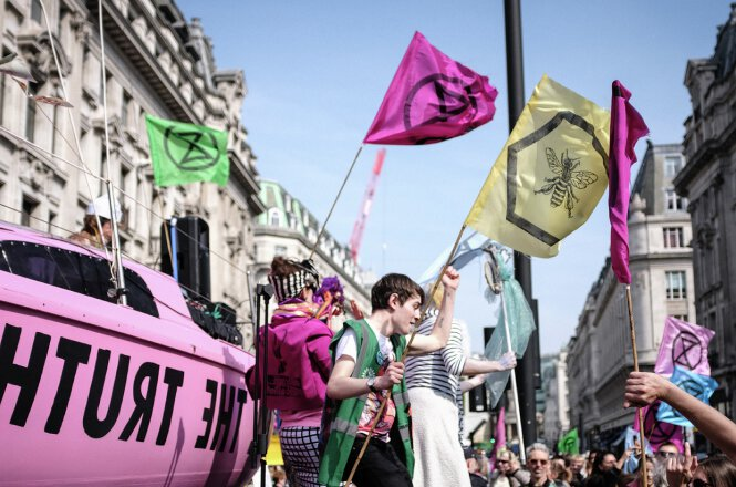 it shows rebels with colorful flags representing bee and extinction rebellion logo