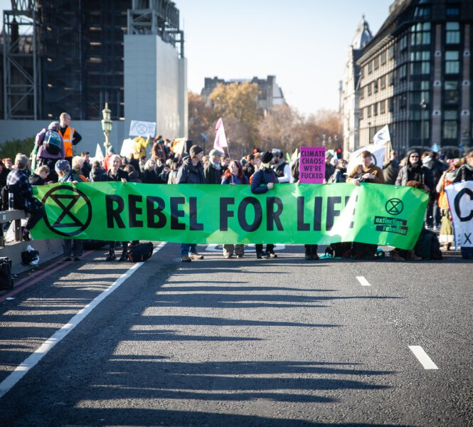 people demonstrating in a street behind a large green banner on which is written rebel for life with extinction rebellion logos