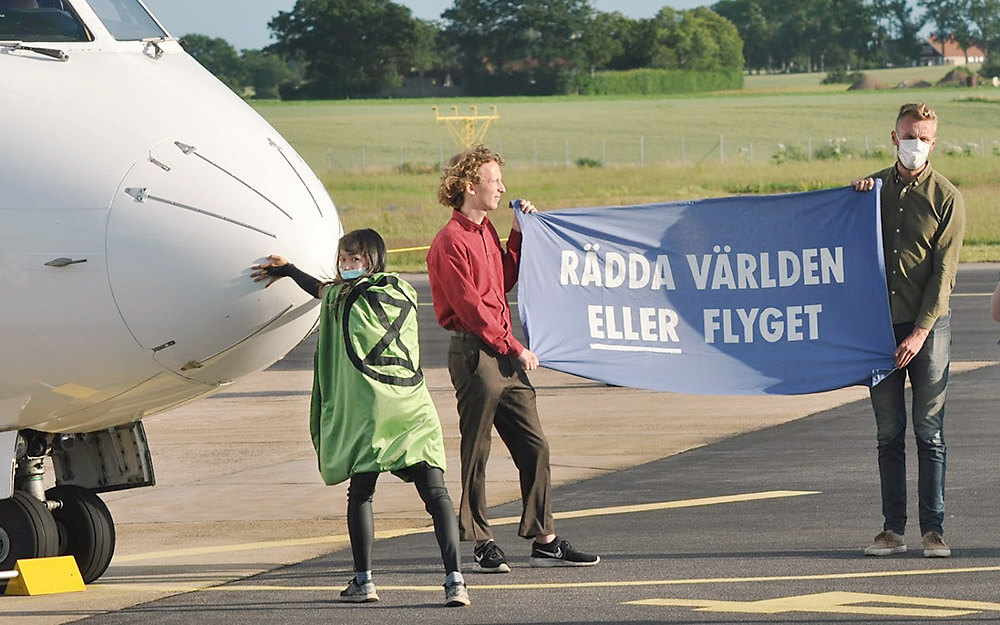 "Photograph of action with rebels holding banner ""Save the world ORaviation."""