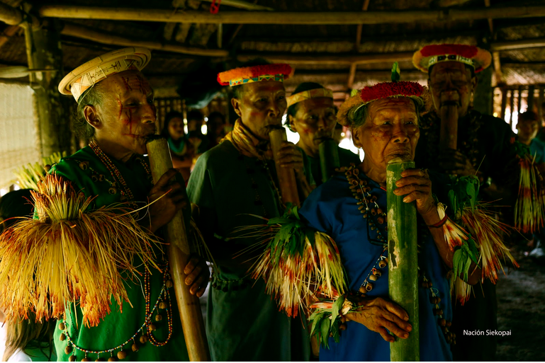 Indigenous elders playing pipes