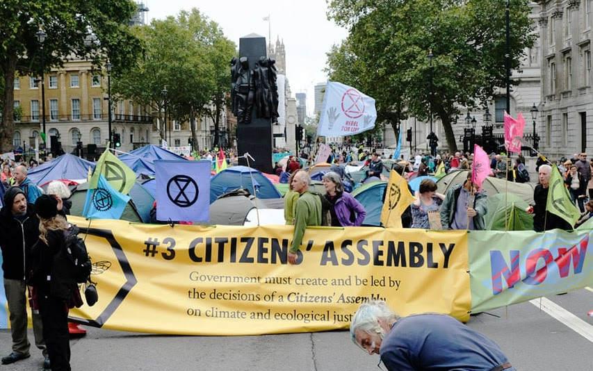 "sprotestors hold up an XR sign reading ""#3 Citizens' Assembly""treet"