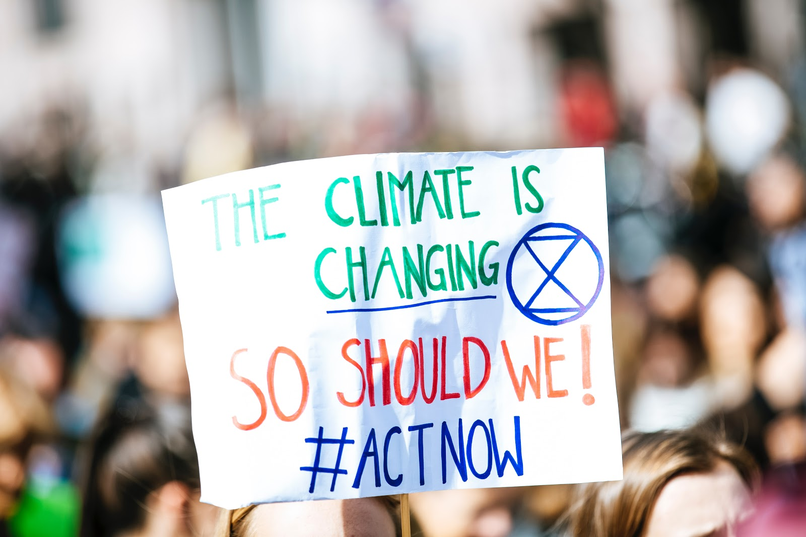 Protest sign with XR logo reading The climate is changing, so should we! #Act now