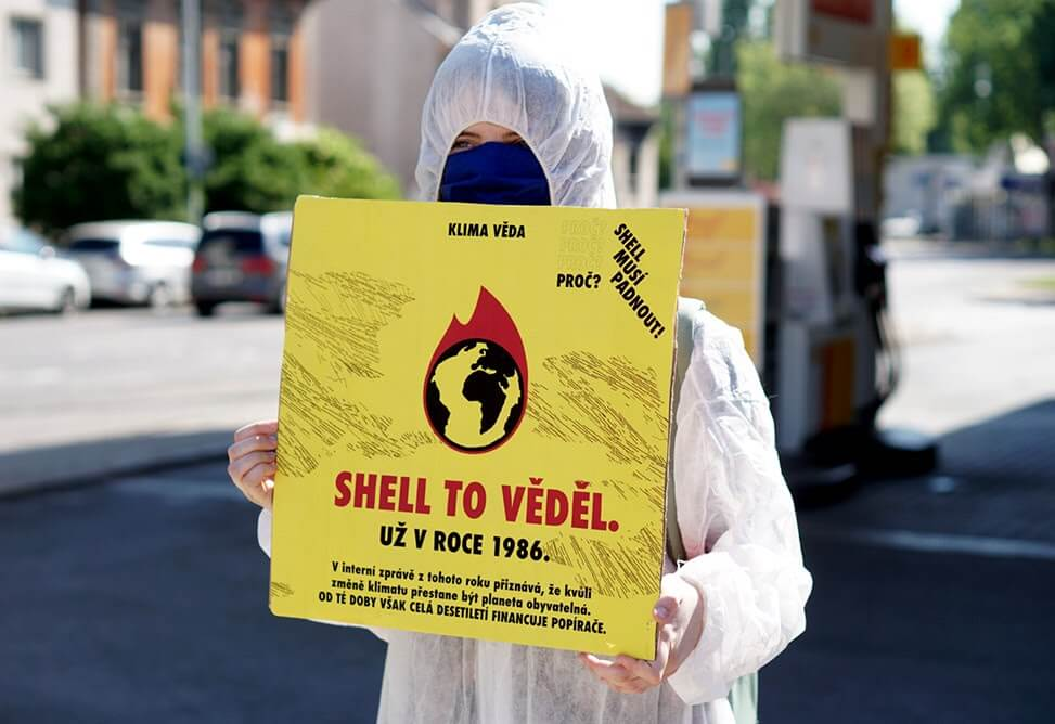 "rebel holding sign saying ""Shell already knew it in 1986"""