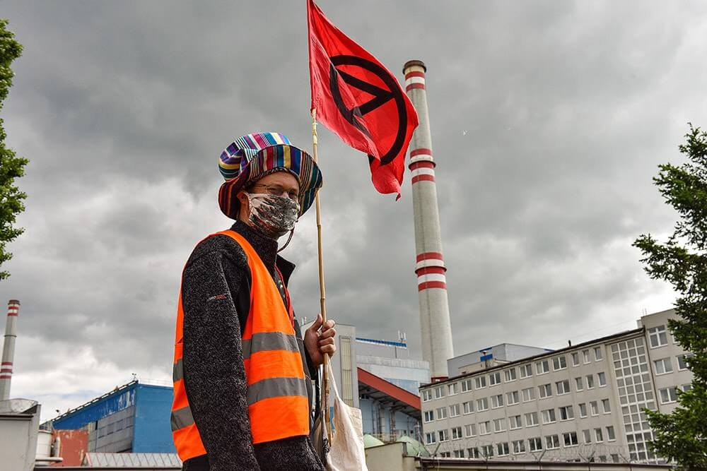 Rebel with an extinction rebellion flag in front of power station