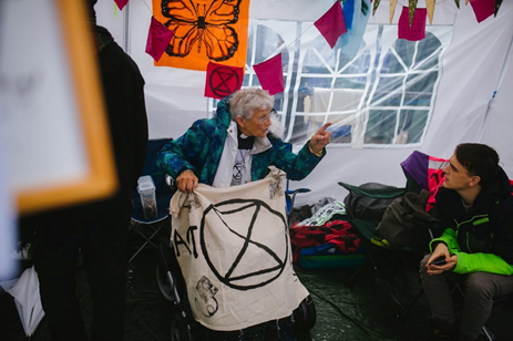 aged clergywoman with a black and white Extinction Rebellion banner having a discussion with a young man at a protest