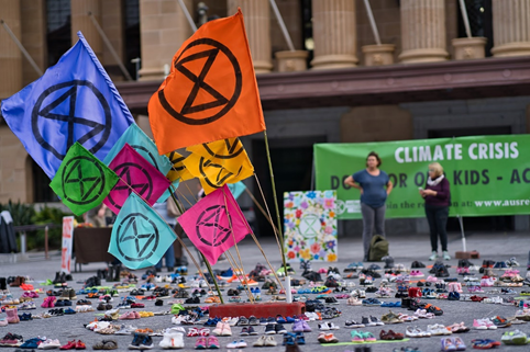 Extinction Rebellion demonstration featuring coloured flags and a display of children's shoes