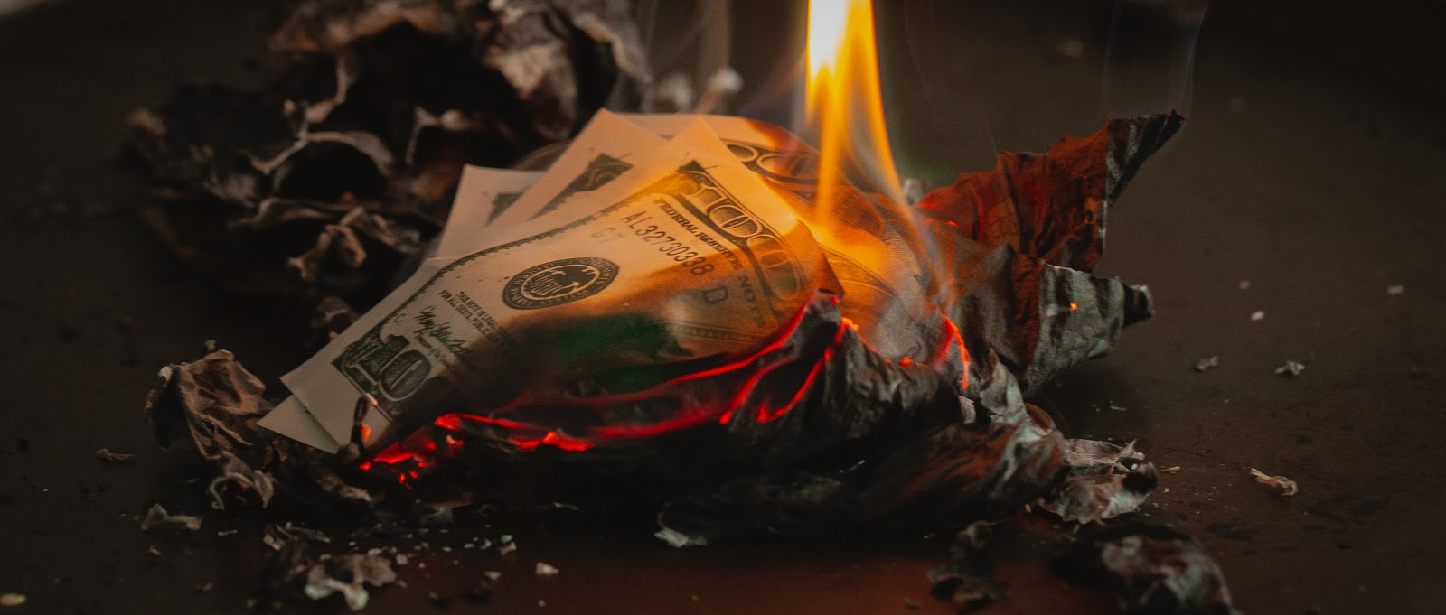 100 US dollar bills burning into ashes