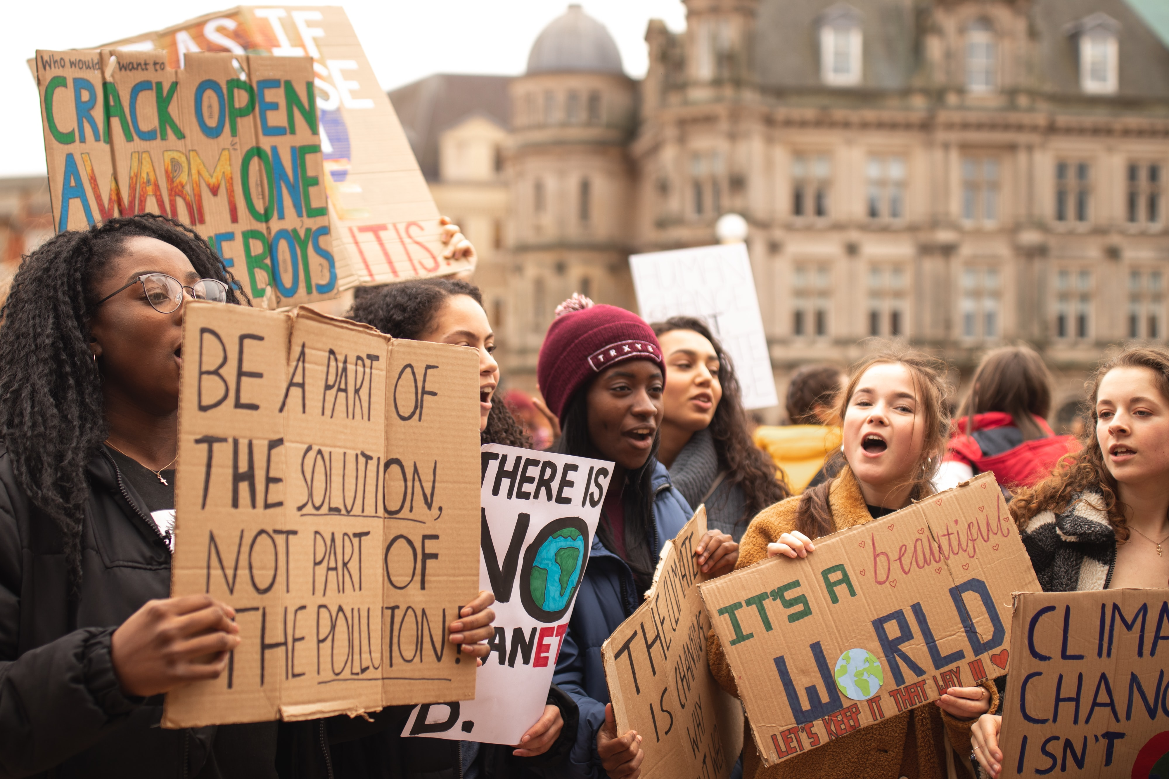 Young women holding climate change protest signs