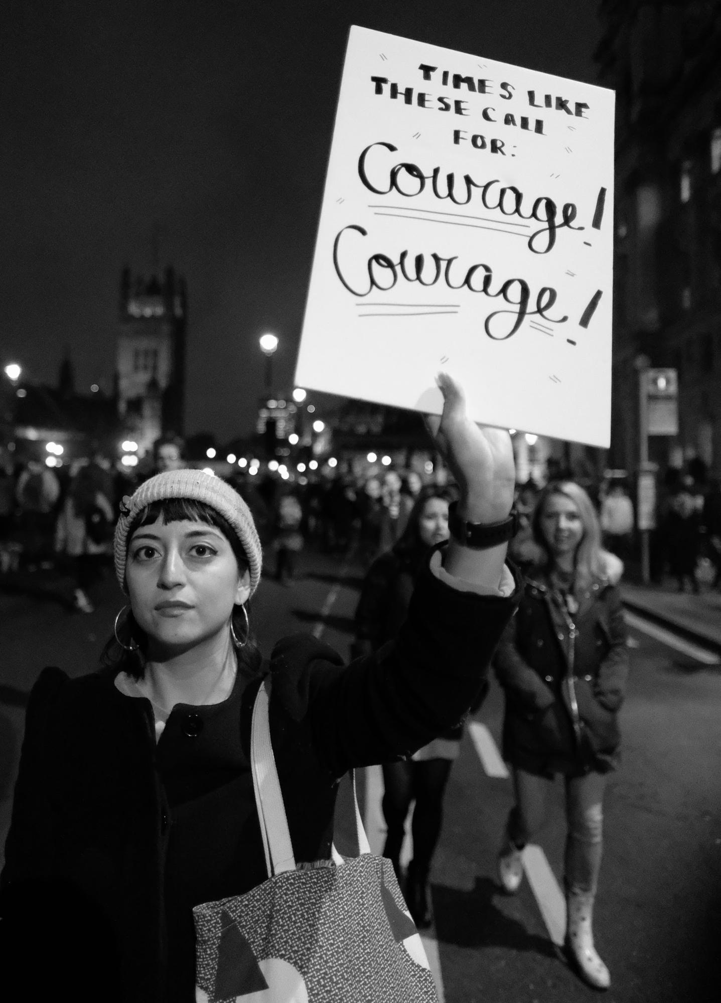 "A woman in a march holds a sign saying ""Times like these call for courage! Courage!"""