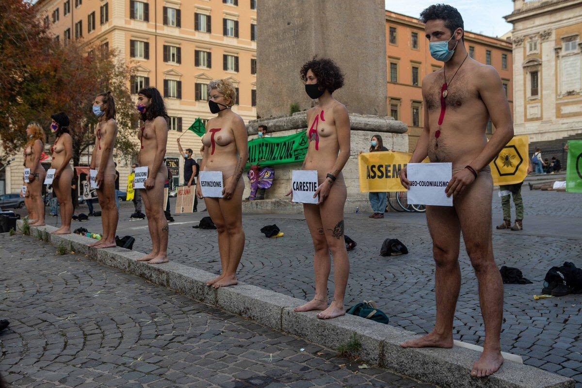Italian rebels standing naked with signs in front of private parts.