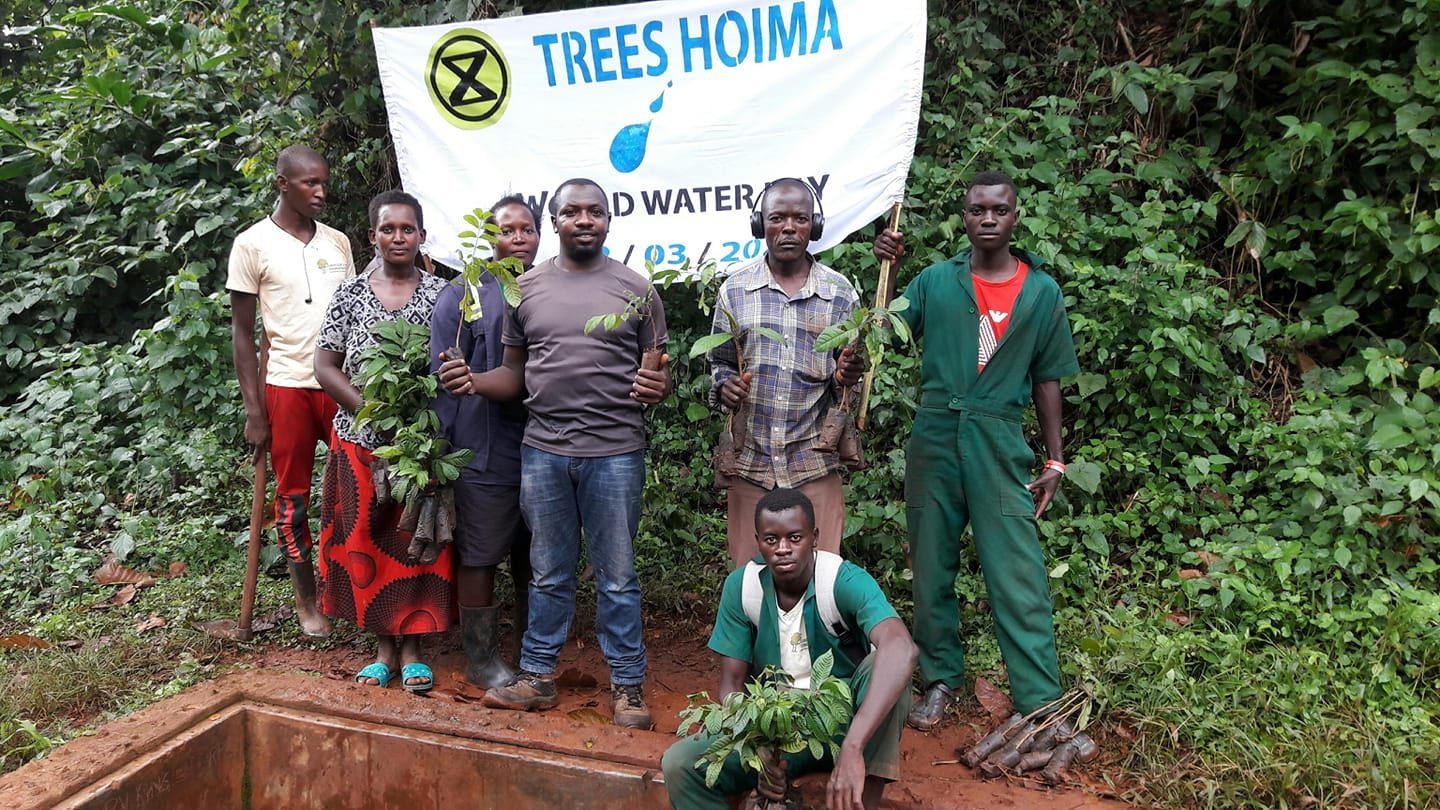 Rebels of XR Uganda hold tree saplings before beginning a tree-planting action.