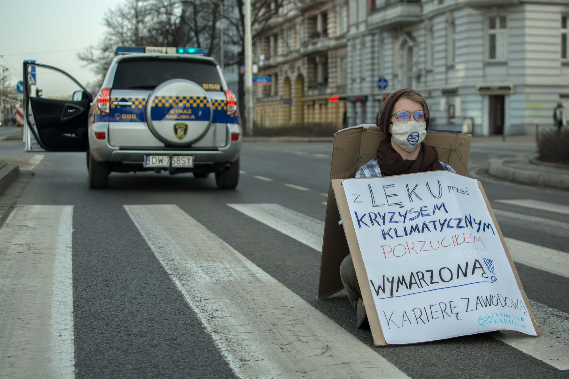 A Rebellion of One in Wrocław. Lone rebels (with hidden support teams) blocked roads across Poland. The banner: 'Climate crisis fears made me drop my dream career'. Photo: cyjon & Alicja Kozuchowska
