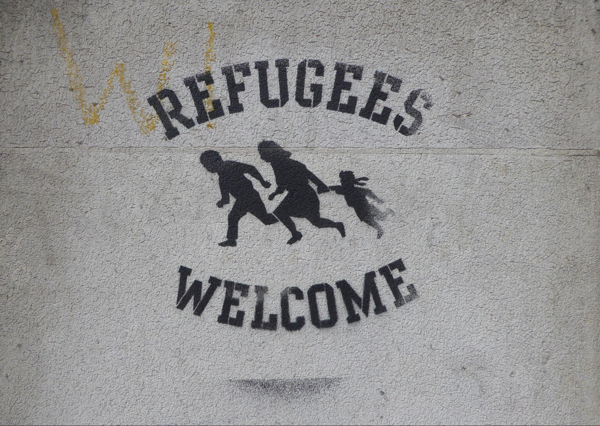 "Sign on wall saying ""Refugees welcome"""
