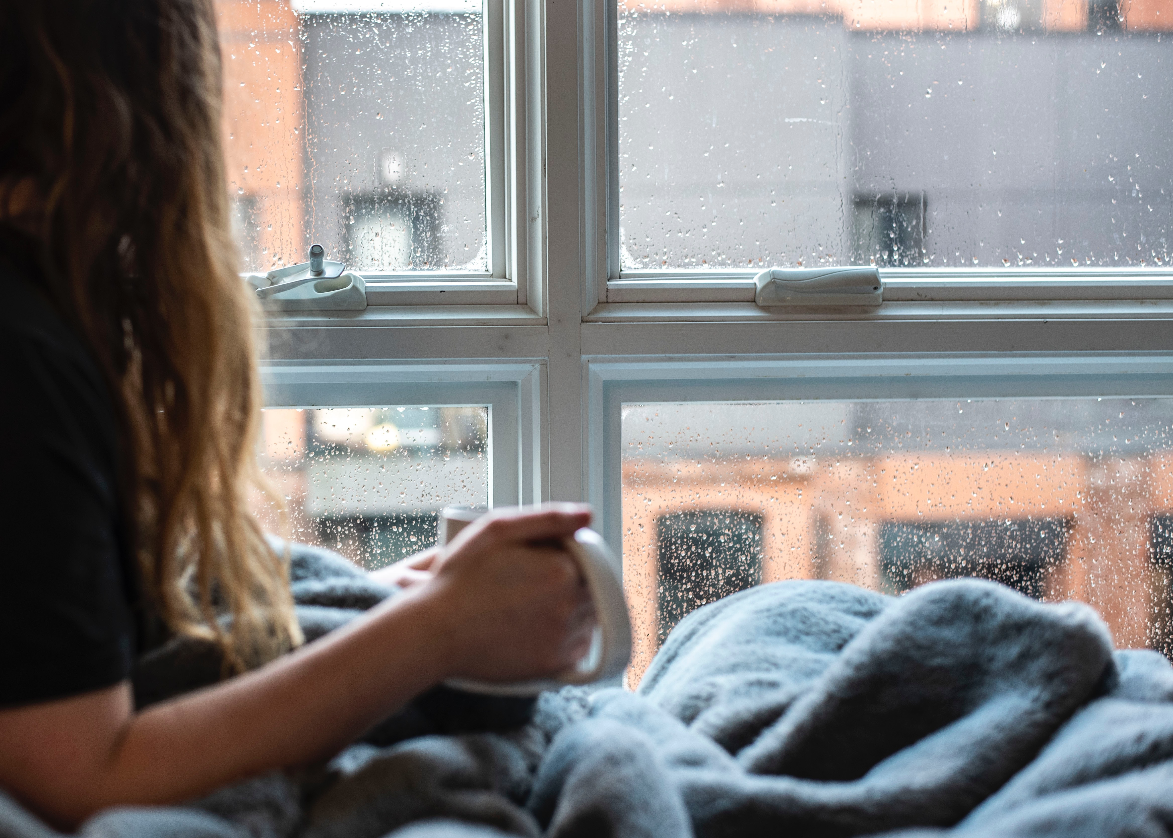 Person seated inside by a rain-spattered window with a blanket and a hot drink