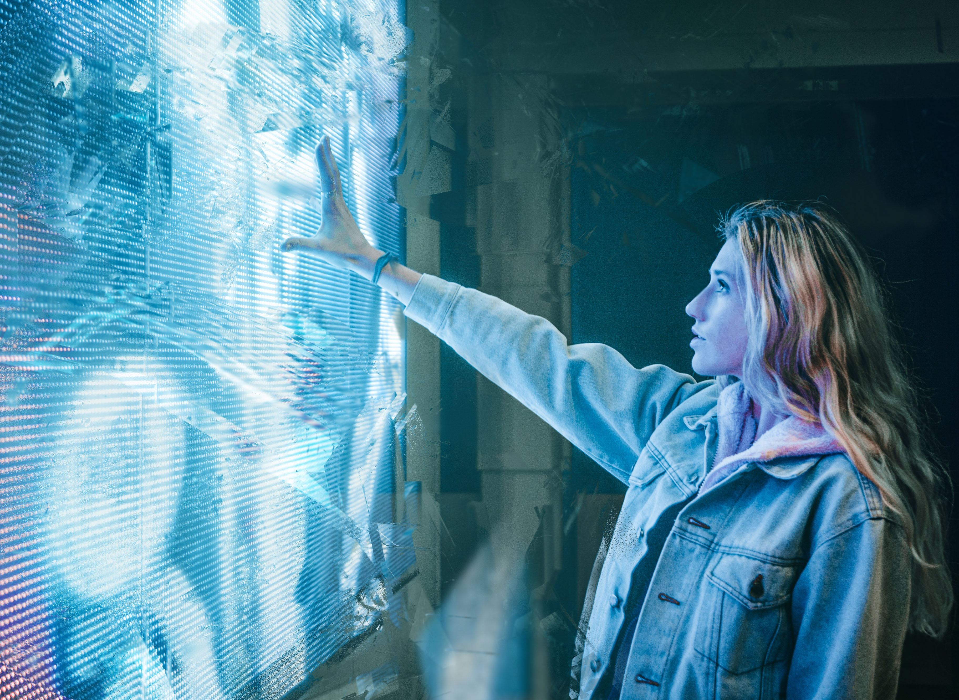 woman placing hand on futuristic-looking wall-sized monitor